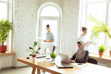 In de dag Hoogte schaal Concentrated. Portrait of a beautiful arabian businesswoman wearing hijab while working at openspace or office. Concept of occupation, freedom in business area, leadership, success, modern solution.