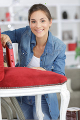 woman fixing a chair with staple