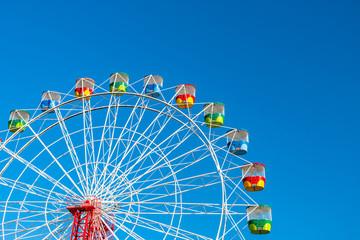 Ferris wheel on clear blue sky background
