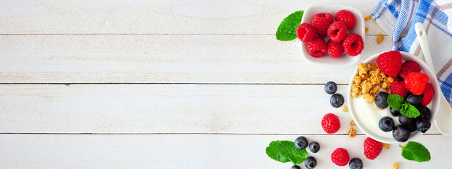 Healthy yogurt with fresh blueberries and raspberries. Banner with side border against a white wood background. Copy space.
