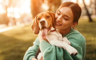 Happy woman embracing beagle dog in park