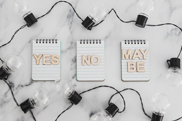 decision making process, group of notepads with yes no and maybe options and string of light bulbs