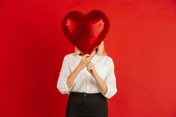 Heart-shaped balloon. Valentine's day celebration, happy, cute caucasian kids isolated on red studio background. Concept of human emotions, facial expression, love, relations, romantic holidays.
