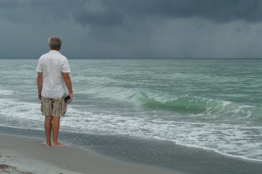 Rear View Of Man Looking At Sea Against Cloudy Sky
