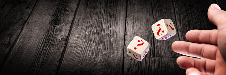 Hand Throwing Two Dice With Red Question Marks Onto Wooden Table