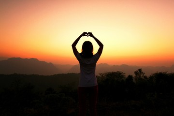 Rear View Of Woman Gesturing Heart Shape While Standing Against Sky During Sunset
