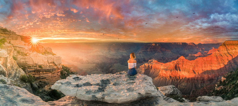 Young woman sitting on the edge of rim and enjoying the Grand Canyon sunset