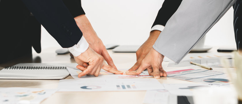 hands and fingers of businesspeople pointing at one point on meeting table in concept of aiming together on same business target
