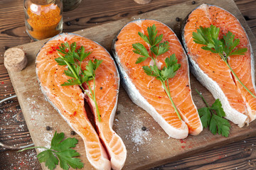 Three raw salmon steaks on a wooden cutting board prepared for cooking, top view