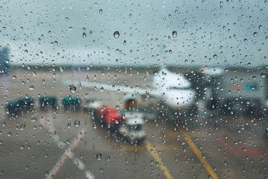 Airplane At Runway Seen Through Wet Window At Airport