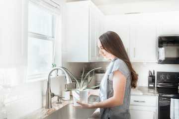 Women holding indoor plant in a white kitchen