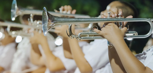 Male student with friends blow the trumpet with the band for performance on stage at night.