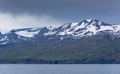 Mountains with snowy pics near the sea on a gloomy day in Iceland