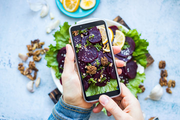 Woman take picture of vegan food with phone at her kitchen. Hand make a closeup smartphone photo of beetroot salad with walnuts for blogging or social media content. Vegetarian healthy food.