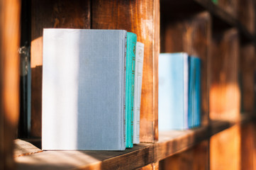 blue and turquoise books without a picture and without a cover close-up stand exactly in a wooden old bookcase