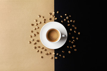 Cup of coffee and coffee beans on gold black background. Creative flat lay. Top view.
