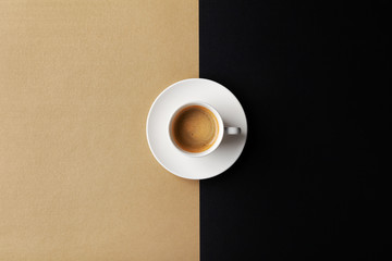 Cup of coffee on gold black background. Minimalistic flat lay. Top view.
