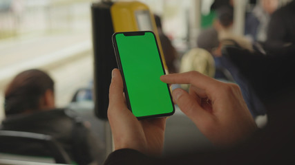 NEW YORK - May 19, 2019: Slow motion man young hand uses holding a mobile telephone with a vertical green screen background tram inside window key smartphone technology touch message display close up