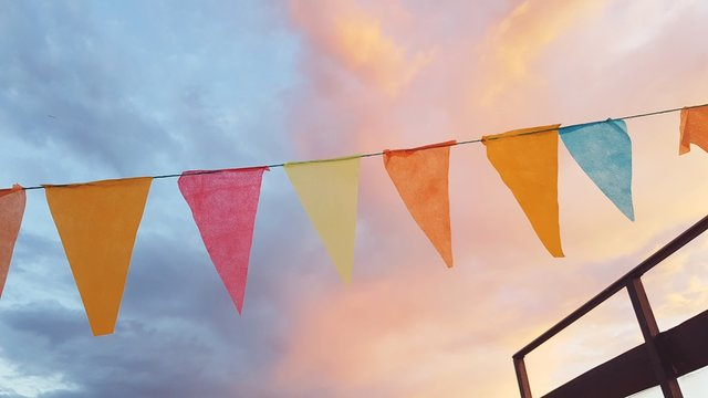 Low Angle View Of Colorful Buntings Against Cloudy Sky During Sunset