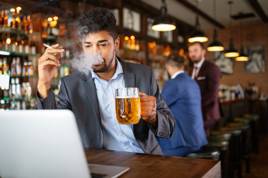 Man drinking beer and smoking cigarette while working on computer. Bad habit concept.