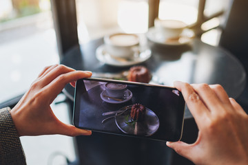 A woman using mobile phone to take a photo of coffee and snack before eat in cafe