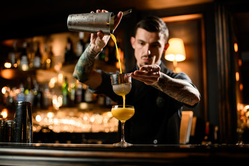 Male bartender pouring a smooth yellow alcoholic cocktail drink from the steel shaker through the sieve