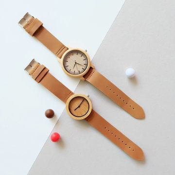 2 wooden watches on white and brown color background