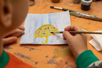 Little boy painting picture by brush on table in kindergarten