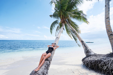 Vacation on the seashore.Young woman in black swimsuit on the beautiful tropical beach laying on the palm tree.