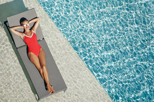 Enjoying suntan. Vacation concept. Top view of slim young woman in red swimwear on the sun lounger near the swimming pool.