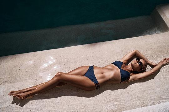 Enjoying suntan and vacation. Top view portrait of pretty young woman in blue swimsuit bikini lying near swimming pool.