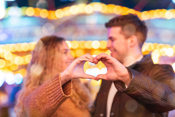 Happy couple in love at amusement park making heart shape with hands