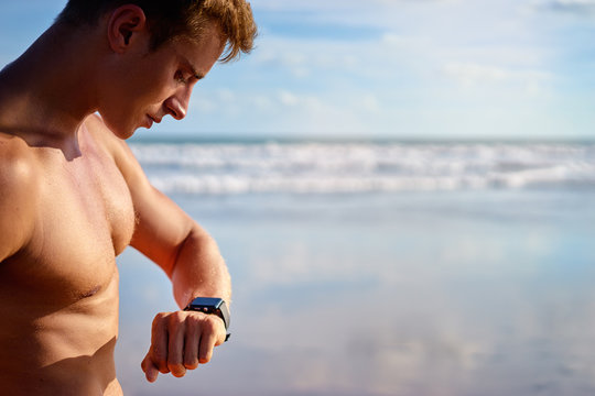 Healthy lifestyle and technology. Young handsome strong man using smart watch tracker on the beach.