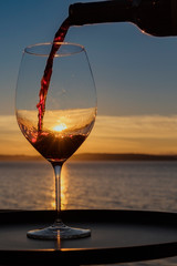Close-Up Of Wineglass Against Sea During Sunset