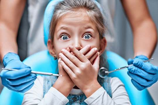 Close up view of a little girl looking scared and terrified screaming covering her mouth from the dentists with medical tools