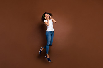 Full size photo of cheerful afro american girl have free time listen playlist music use green headset enjoy stereo sound jump wear stylish white t-shirt isolated over brown color background