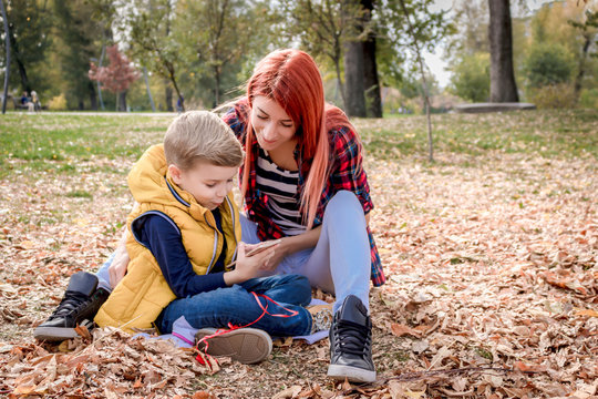 Mother and son using cell phone while relaxing in autumn leaves.