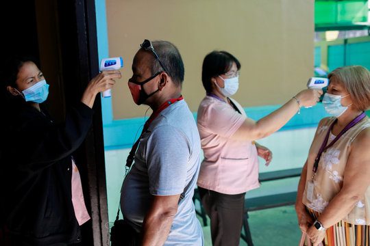 Faculty members wearing masks use thermometers to check the temperature of guardians fetching students, amid a health scare over a new virus that has infected thousands since emerging in China, in a Chinese school in Quezon City