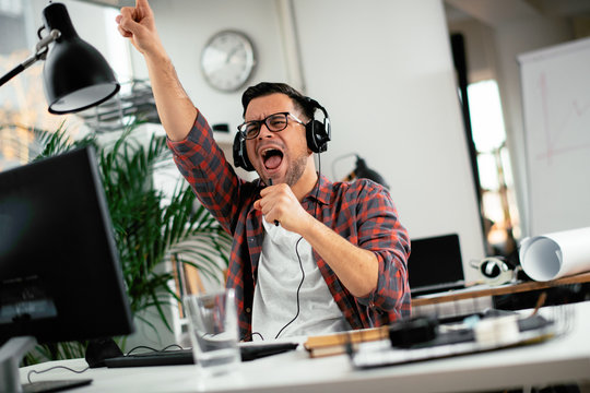 Attractive businessman in office. Young programmer with headphones singing at work.