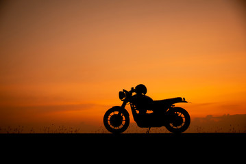 Silhouette of motorcycle parking with sunset background in Thailand,Young Traveller man placed helmet on motorbike.Trip and lifestyle of Motorcycle Concept. Papier Peint