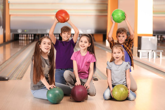 Happy children with balls in bowling club