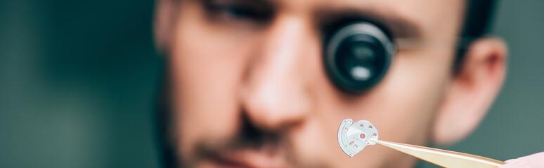 Selective focus of watchmaker holding watch part with tweezers, panoramic shot