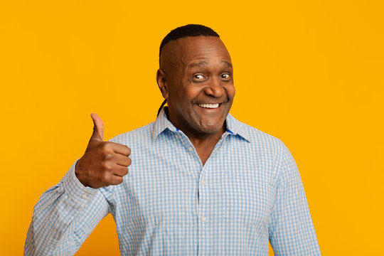 Happy middle aged african man gesturing thumb up