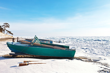 Baikal Lake in the winter. Fishing boats on a snowy shore. The frozen lake is covered with ice hummocks. Winter landscape