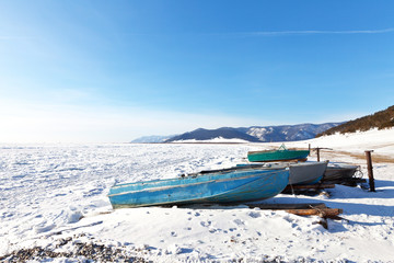 The coast of Baikal Lake on a frosty winter day. Fishing boats on a snowy beach. Ice hummocks cover the surface of the lake. Beautiful winter landscape. Natural background