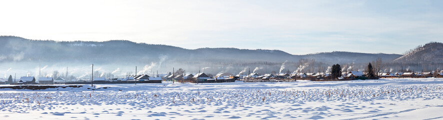 Siberian village on a frosty January morning. Baikal region. Panoramic view of the village of Maloye Goloustnoye. The villagers heat the wooden houses with stove heating. Rural winter landscape