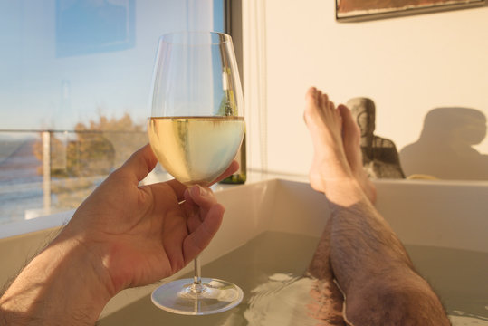 Low Section Of Man Holding Wine Glass While Sitting In Bathtub