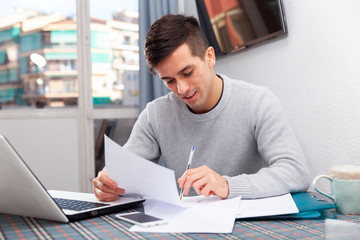 Young happy man sitting at home table working with papers, analyzing domestic budget