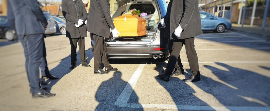 Gravediggers put coffin into car