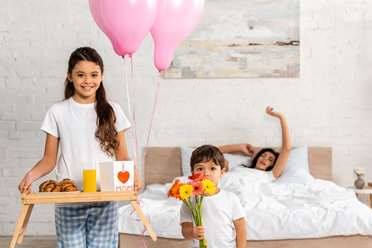 cute girl holding tray with breakfast and mothers day card with heart sign and mom lettering, and boy holding bouquet while mother stretching in bed